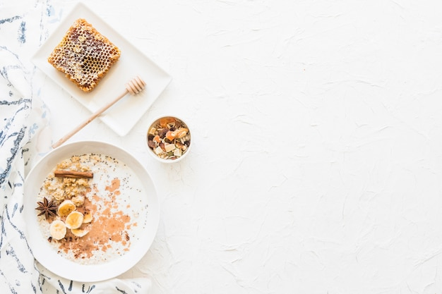 Overhead view of oats healthy breakfast and dryfruits on textured white background Free Photo