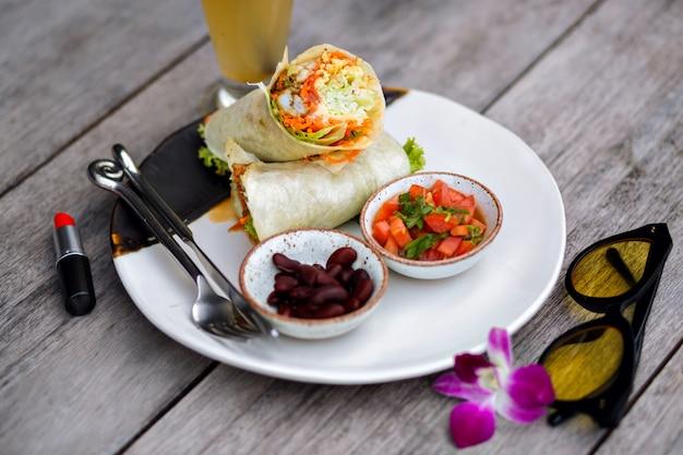Вид сверху красной помады, еды и фиолетового цветка на деревянном столе. фотография большой тарелки с вкусным салатом и фасолью, стоящей рядом со стаканом смузи. Бесплатные Фотографии