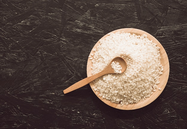 Overhead view of wooden bowl rice grains with spoon 23 2147883400