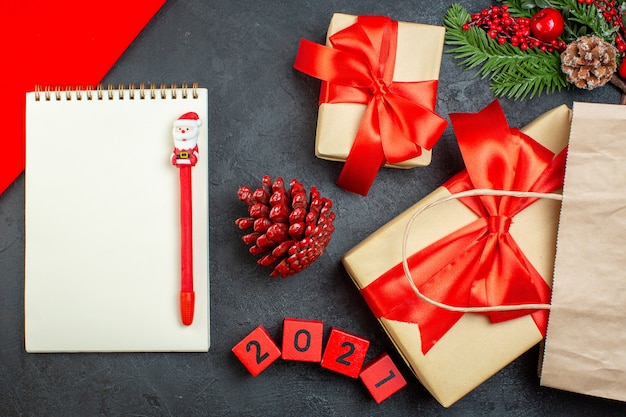 Вид сверху на блокнот рождественского настроения с ручкой из хвойных шишек и числами подарочных еловых веток на темном столе Бесплатные Фотографии