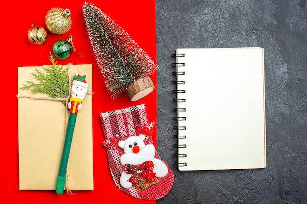 빨간색과 검은 색 Backgroud에 노트북 옆에 크리스마스 트리 장식 액세서리 선물 양말과 함께 크리스마스 분위기의 오버 헤드보기 무료 사진