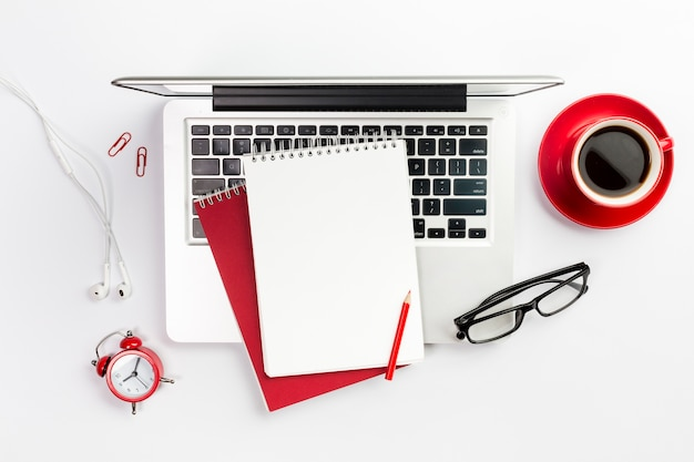 Overhead view of office supplies,laptop,coffee cup,alarm clock and spectacles over white desk Free Photo