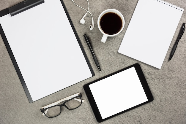 An overhead view of office supplies with coffee cup and digital tablet on gray desk Free Photo