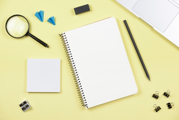 An overhead view of office supplies with laptop on yellow background Free Photo