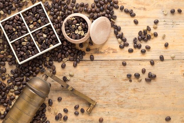 An overhead view of old coffee grinder with coffee beans in container and table Free Photo
