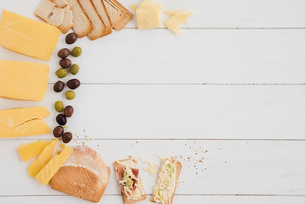 An overhead view of olives; cheese slice and bread on white wooden table Free Photo