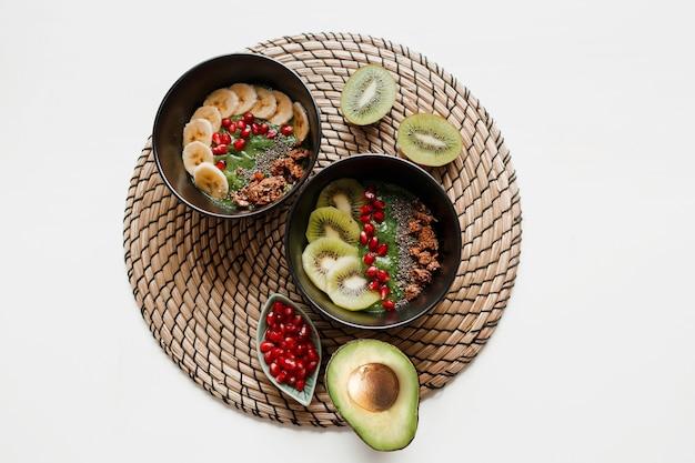 Вид сверху на тарелку зеленой миски для смузи, увенчанной авокадо и шпинатом, зернами граната и мюсли. Бесплатные Фотографии