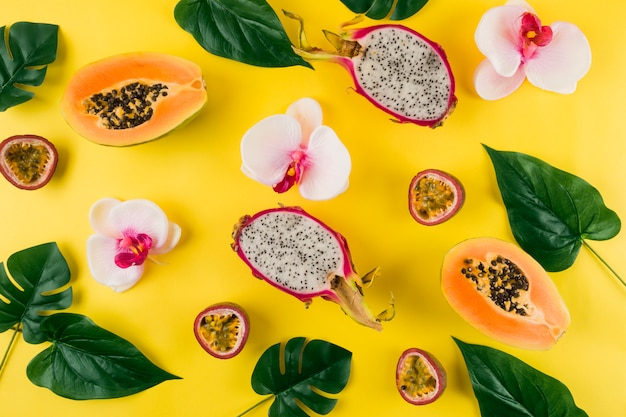 An overhead view of orchid flower; leaves; dragon fruit and papaya on yellow backdrop Free Photo