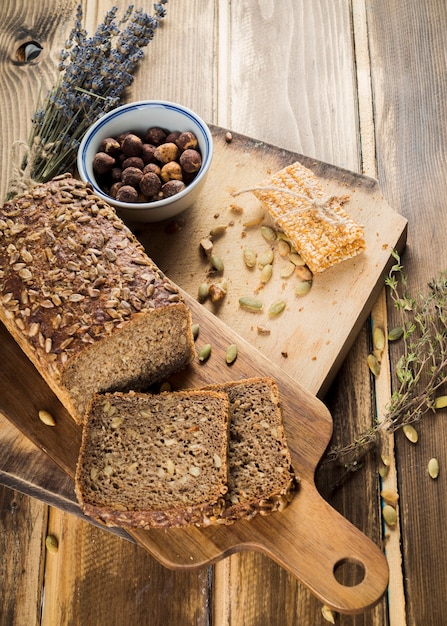 An overhead view of organic bread and energy bar on chopping board Free Photo