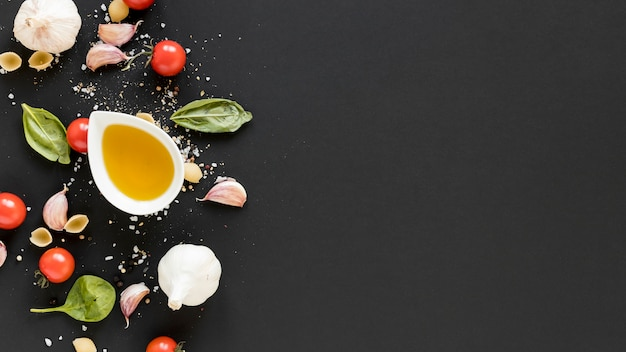Overhead view of organic cherry tomato; basil leaves; garlic and bowl of olive oil over black surface Free Photo