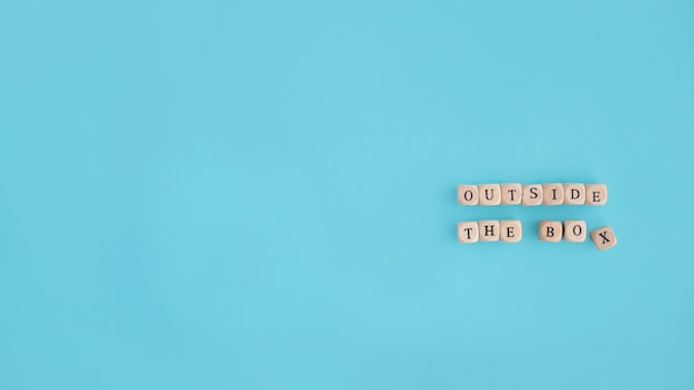 Overhead view of outside the box text blocks on blue background Free Photo