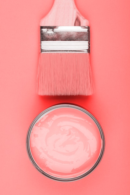 An overhead view of paint coral and paintbrush on colored background Free Photo
