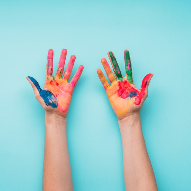 Overhead view of a painted hands on blue backdrop Free Photo