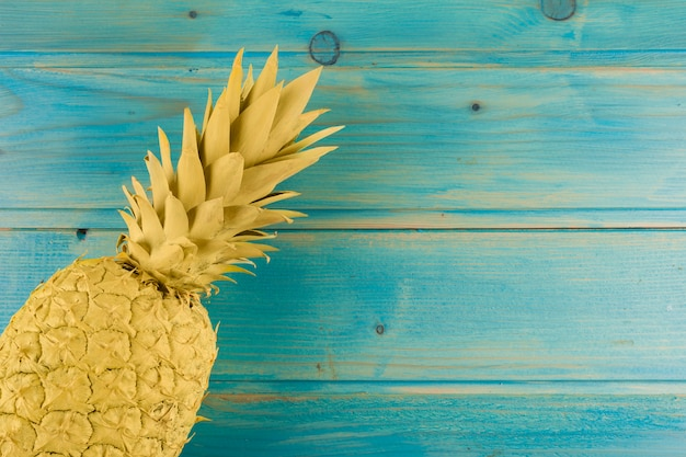 An overhead view of painted pineapple on turquoise table Free Photo