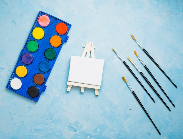 Overhead view of painting equipment on blue backdrop Free Photo