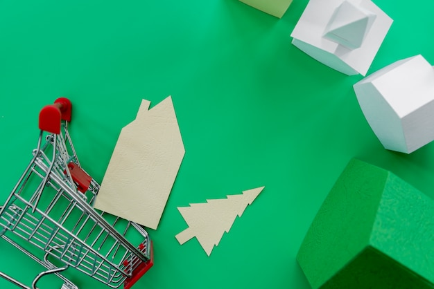 An overhead view of paper houses with shopping trolley on green background Free Photo