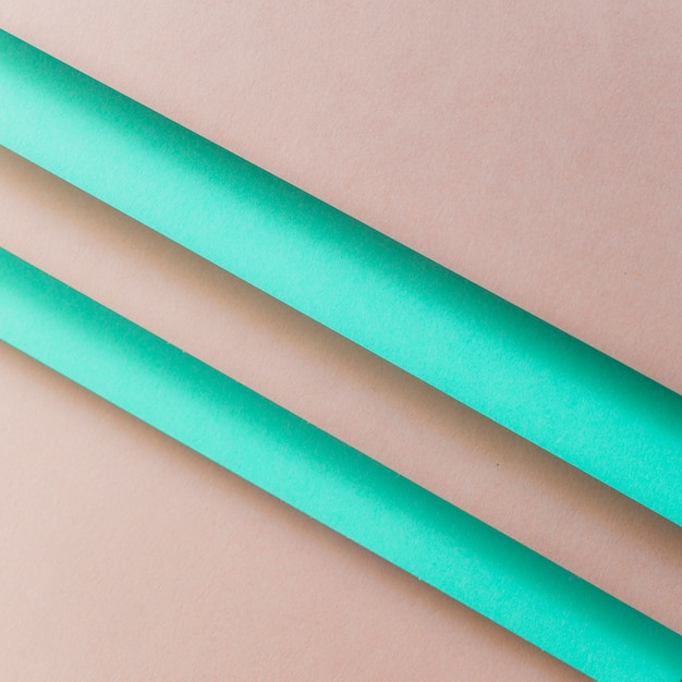 An overhead view of paper turquoise stripes over the brown backdrop Free Photo