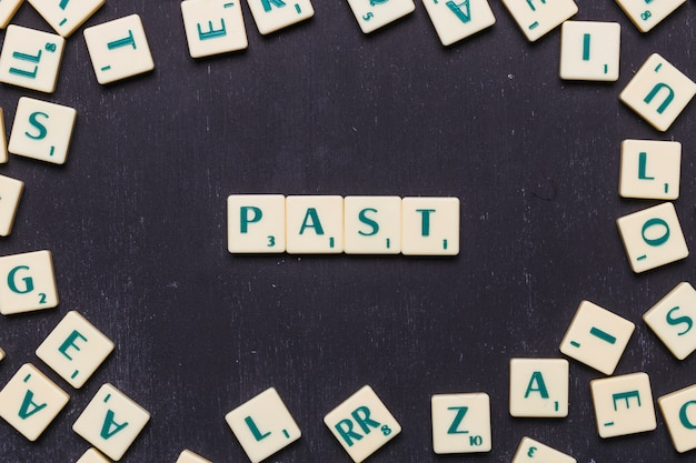 Overhead view of past text on scrabble letters over black backdrop Free Photo