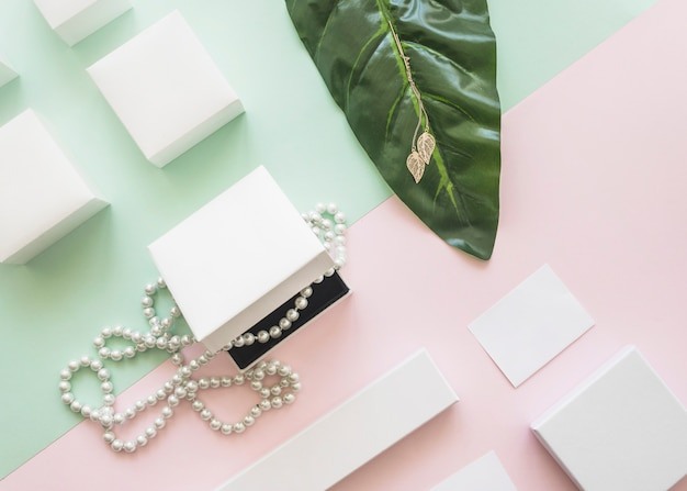 Overhead view of pearl necklace and golden earrings with white boxes on paper background Free Photo