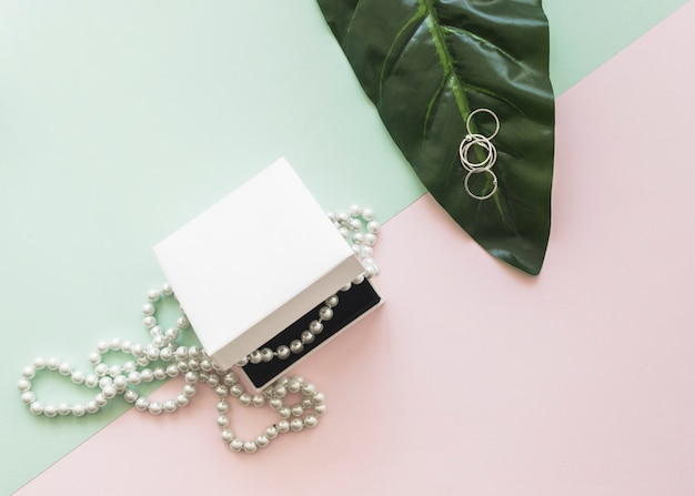Overhead view of pearl necklace in white box and rings on leaf over the pastel background Free Photo