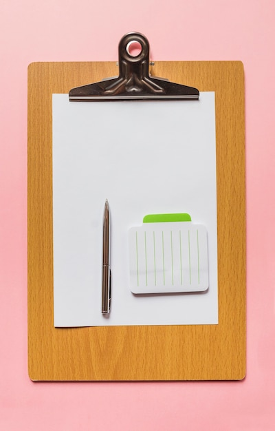 An overhead view of pen and notepad on blank paper over wooden clipboard against pink background Free Photo