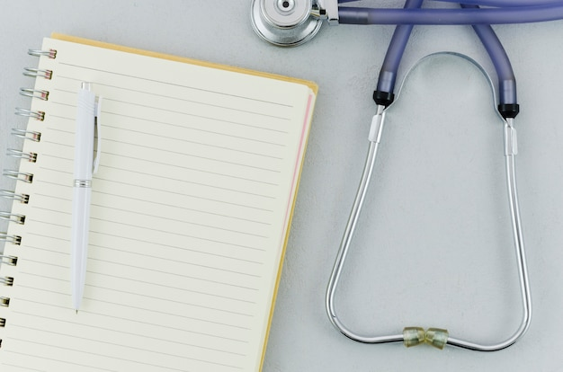 An overhead view of pen over spiral notebook and stethoscope on grey background Free Photo