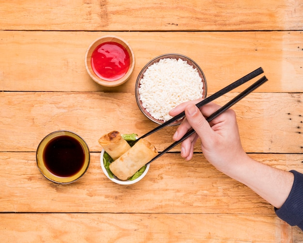 An overhead view of a person picking the spring roll with chopsticks on wooden desk Free Photo