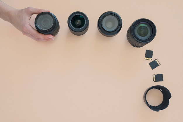 Overhead view of person's hand arranging camera lens; memory card and extension rings over colored background Free Photo