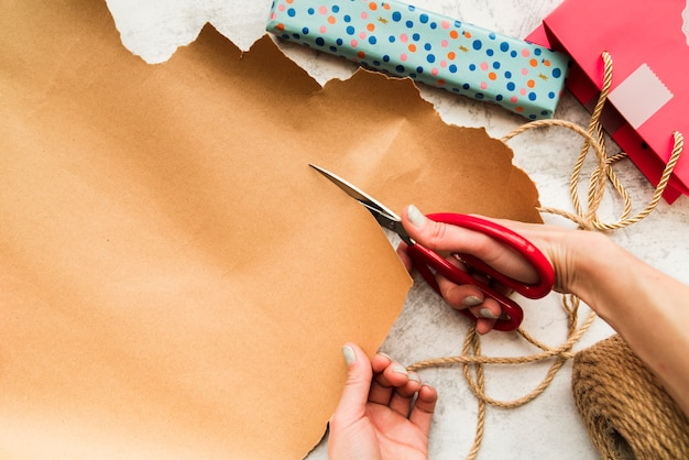 An overhead view of a person 's hand cutting the brown paper with scissor Free Photo