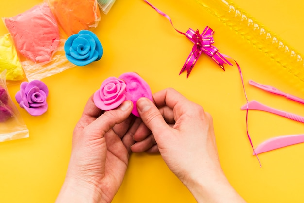 An overhead view of a person's hand making the colorful pink rose on yellow backdrop Free Photo
