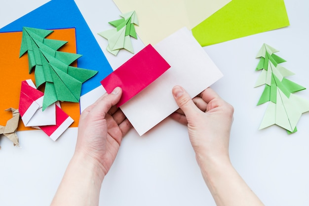 An overhead view of a person's hand making the craft with paper on white backdrop Free Photo