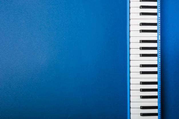 An overhead view of piano keyboard on blue background Free Photo