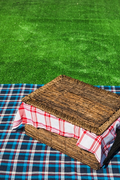 An overhead view of picnic basket on checkered table over green turf Free Photo