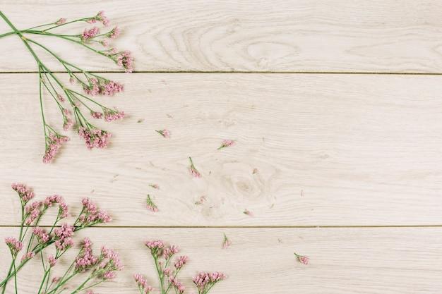 Una vista aerea dei fiori rosa limonium su superficie strutturata in legno Foto Gratuite