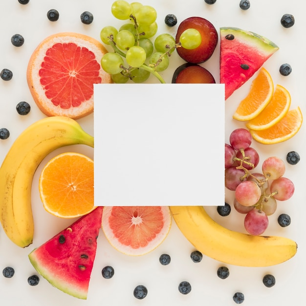 An overhead view of placard over the fresh healthy fruits on white backdrop Free Photo