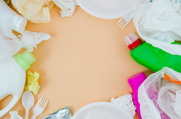 Overhead view of plastic garbage over beige background Free Photo