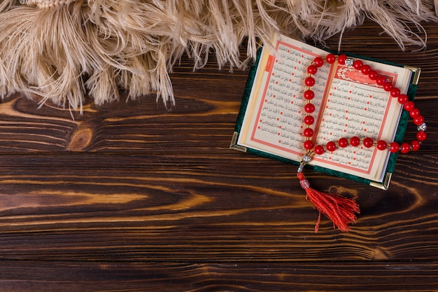 An overhead view of prayer beads with islamic holy book on wooden desk Free Photo
