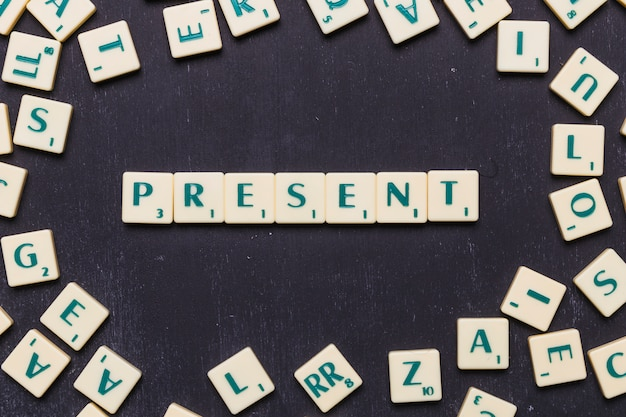 Overhead view of present text on scrabble letters over black backdrop Free Photo