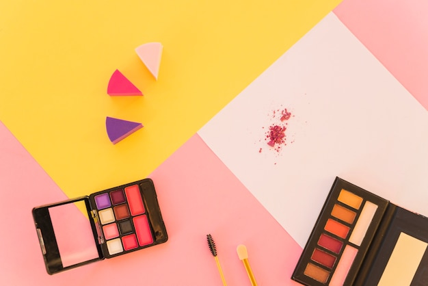 An overhead view of professional make-up tools and eyeshadow palette on colorful background Free Photo