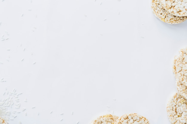 An overhead view of puffed rice cakes with grains on white paper Free Photo