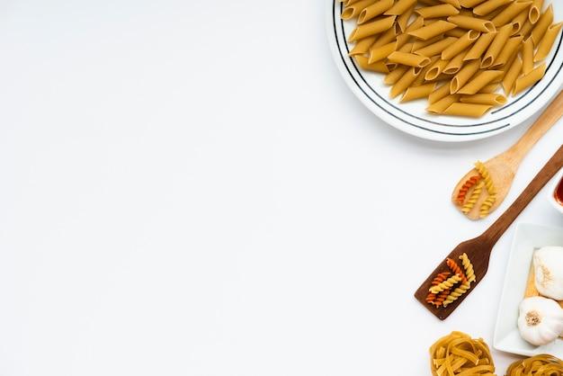 Overhead view of raw italian pasta over white background Free Photo