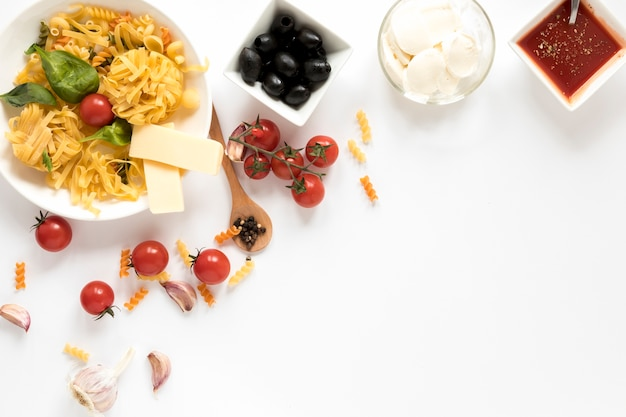 Overhead view of raw pasta and it's ingredients isolated over white surface Free Photo