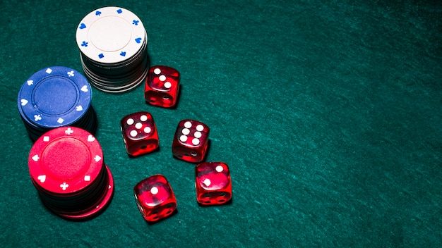 Overhead view of red dices and casino chip stacks on green poker table Free Photo