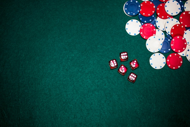 Overhead view of red dices and casino chips on green poker background Free Photo