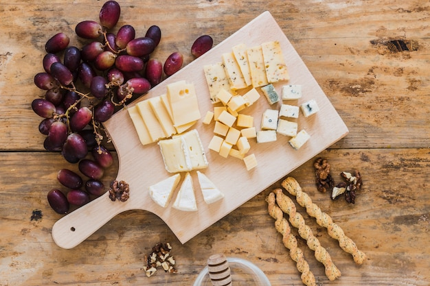 An overhead view of red grapes, variety of cheese, bread sticks on wooden desk Free Photo