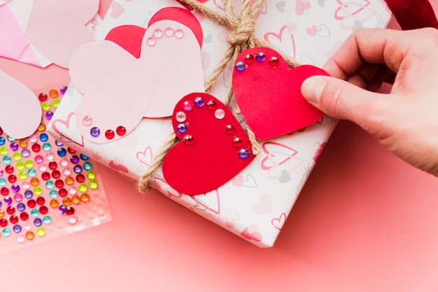 An overhead view of red and pink heart shape on wrapped gift box Free Photo