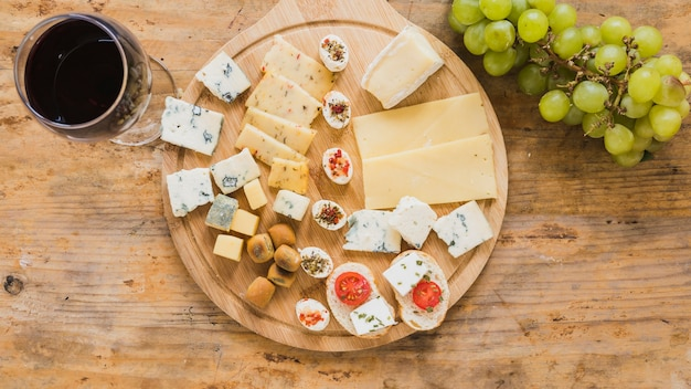 An overhead view of red wine glass with cheese blocks and tomatoes on wooden desk Free Photo