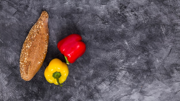 An overhead view of red and yellow bell peppers with loaf of bread against black textured background Free Photo