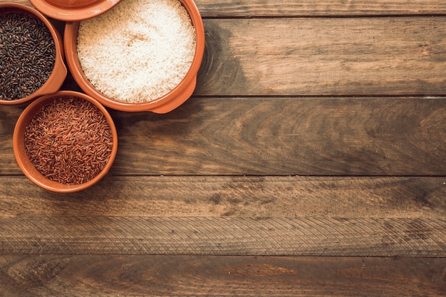 Overhead view of rice grains in the bowl on wooden table Free Photo