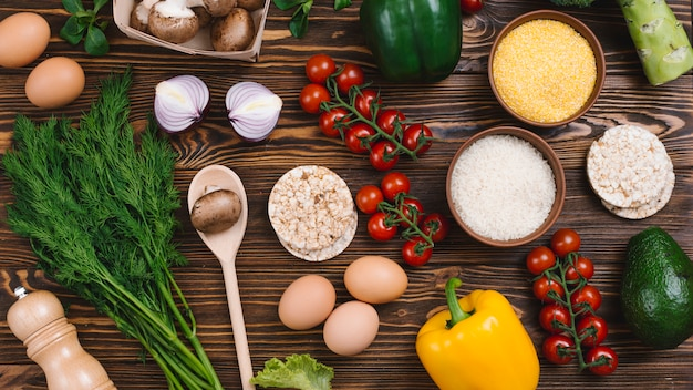 An overhead view of rice grains; polenta; puffed rice cake and vegetables on wooden table Free Photo